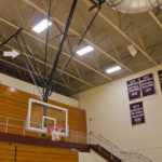 Basketball backstop with safety strap